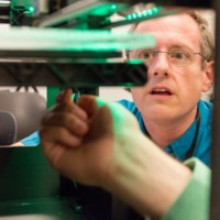 Man looking at 3d printer, THATCamp 2013 (Jun 7 2013).jpg